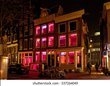 Amsterdam, Holland, December 2016: Prostitutes in their red-lit windows luring customers in the red light district