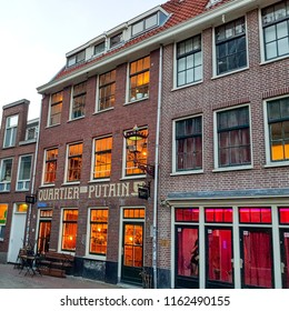 Amsterdam, Holland, February 28, 2018: Quartier Putain - Amsterdam's red lights district near Oude Kerk (Old Church). Cityscape - walking along the old streets and canals in frosty winter day.
