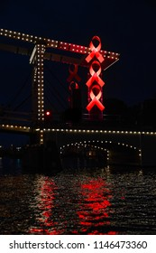 Amsterdam / Holland - July 30, 2018: Red Aids ribbons on the Magere Brug (Skinny Bridge) in Amsterdam welcome visitors of the AIDS Conference 2018. They will also be visible during Gay Pride 2018.