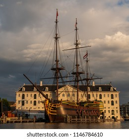 "AMSTERDAM, HOLLAND - JULY 30, 2018: The replica of the three masted Doen VOC ship ""Amsterdam""in front of the National Maritime museum in Amsterdam, seen from the IJ water at sunset."