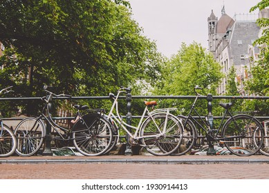 Amsterdam, Holland, May 12 2018: Old bicycle parked on a canal bridge in Amsterdam