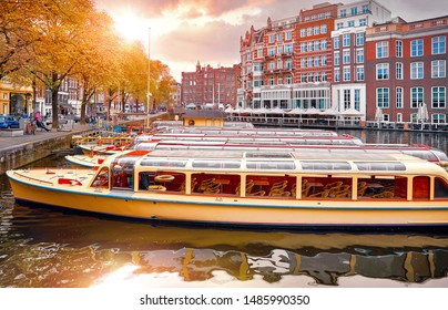 Amsterdam, Holland, Netherlands. Amstel river, canals and boats against evening dusk sunset sky cityscape. Pleasure boat for touristic tour.