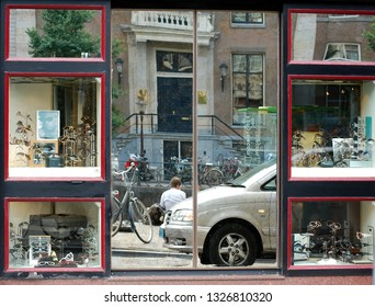AMSTERDAM, HOLLAND — NETHERLANDS — JUNE 26, 2010:  Amsterdam, Netherlands. The reflection of the city in the optics store showcase
