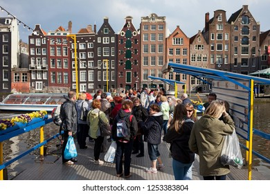 Amsterdam, Holland, Netherlands - May 11, 2013: Group of tourists waiting on canal pier for boat tours and cruises around the Old Town