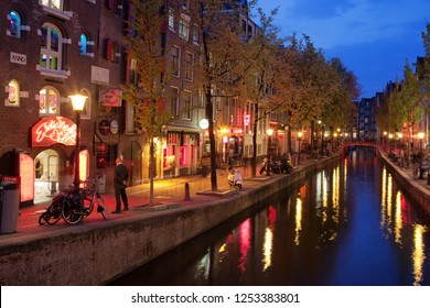 Amsterdam, Holland, Netherlands - May 13, 2013: Famous Red Light District and canal in historic city center at night, on the left Erotic Museum