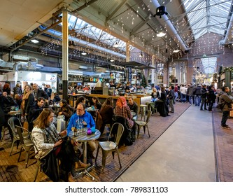 Amsterdam, January 2018. Crowded bar in an old industrial building called de Hallen, with mainly young people having a drink at the tables and at the bar