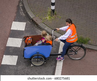 Amsterdam, July 2017. Woman with high visibility vest riding a carrier cycle with two young children as passengers