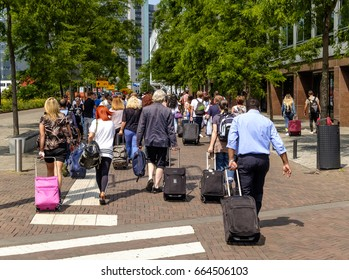 Amsterdam, June 2017. Large group of people walking along a footpath, dragging their trolley suitcases and carrying bags