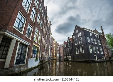 AMSTERDAM - JUNE 24, 2018: View of the famous canal area in Amsterdam, The Netherlands on 24 June 2018. The canal area is an UNESCO world heritage site since year 2010.