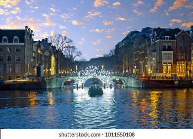 Amsterdam lights in the city center at the river Amstel in the Netherlands at sunset