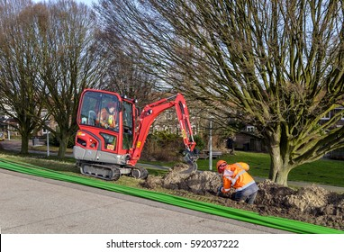 Amsterdam, March 2017. Construction workers laying glass fiber cable. One is inside the ditch, the other is operating a small excavator