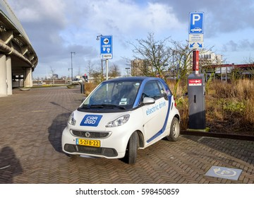 Amsterdam, March 2017. Electrical car from the Car2Go car sharing service at a parking place, plugged into a battery charging station