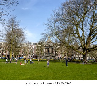 Amsterdam, March 2017. Group of twelve young children playing on the grass in a park, with flowers, a monument and houses in the background