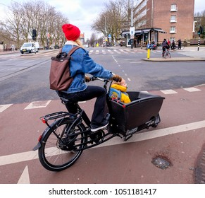 Amsterdam, March 2018. mother with her young child in a criier bike, is waiting to cross the road