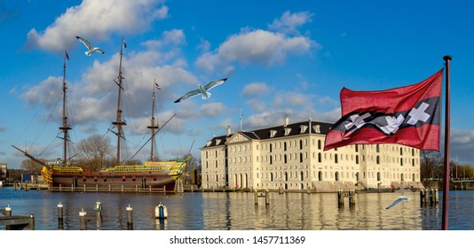The Amsterdam marine skyline with city flag, seagulls and modern replica of a historic three-masted sail clipper moored near the Maritime Museum, the Netherlands tourist landmarks.