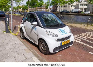 Amsterdam, May 2018. Electrical car from the international Car2Go car sharing service at a parking place, plugged into a battery charging station