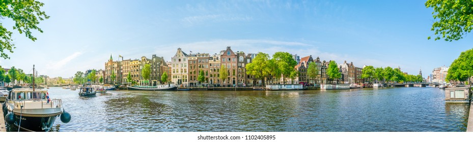 Amsterdam, May 27 2018 - Panorama view on the river Amstel filled with small boats and traditional houses in the background on a summer day
