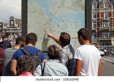 AMSTERDAM, NEDERLANDS - SEPTEMBER 7, 2014: People use urban navigation map, pointing the place on the map