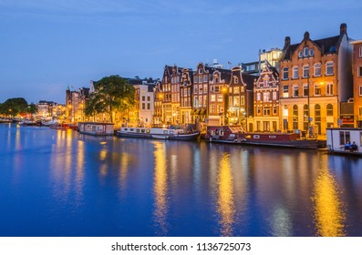 AMSTERDAM, NETHERLAND ; JULY 2018. Houses and canal signature of Amsterdam at night.