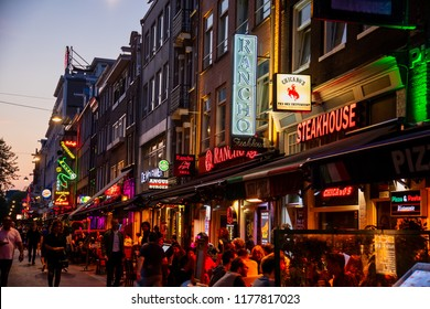 Amsterdam, Netherland - July 7, 2018: Colorful night lights with music entertainment and bars in walking street Korte Leidsedwarsstraat at Amsterdam. is a busy tourist street.
