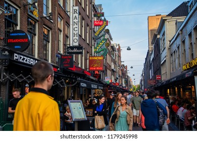 Amsterdam, Netherland - July 7, 2018: Bars and coffee shops on the street full of tourists at night in famous Red Light District in Amsterdam, Netherlands.