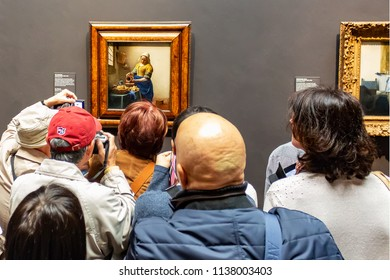 Amsterdam / Netherlands - 03 28 2014: Visitors looking at the painting milkmaid by Johannes Vermeer