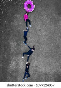 Amsterdam / Netherlands  - 05.27.2018 : Creative drone shot from above . girls holding on a donut gravity illusion . laying on grass