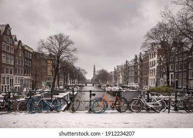 Amsterdam, The Netherlands, 07 February 2021: old historic city center of Amsterdam under the snow emptied of tourists as Covid-19 measures have made the number of visitors decrease