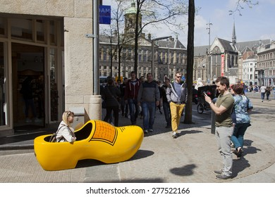 Amsterdam, Netherlands, 10 may 2015: man takes picture of woman in giant yellow clog in amsterdam on Dam Square