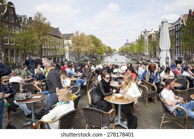 Amsterdam, Netherlands, 10 may 2015: People enjoy nice spring day on a bridge over Singel canal in Amsterdam