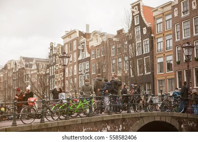 Amsterdam, Netherlands, 11 December 2016 - a group of friends doing pictures on a bridge in Amsterdam