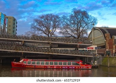 AMSTERDAM, NETHERLANDS, 11 MARCH 2017: Tourist boat parked alongisde bicycle parked area. Amsterdam is the capital and most popular municipality of the Netherlands