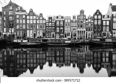 AMSTERDAM, NETHERLANDS - 16TH FEBRUARY 2016: A view of buildings and boats along the Amsterdam Canals. Reflections can be seen in the water.