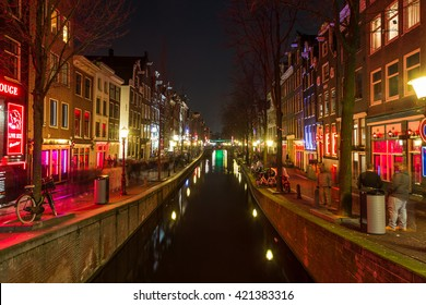 AMSTERDAM, NETHERLANDS - 17TH FEBRUARY 2016: A view along the Oudezijds Achterburgwal Canal in the De Wallen District in Amsterdam at night.