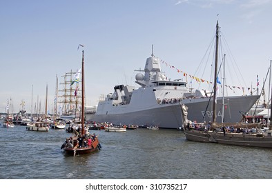 AMSTERDAM, THE NETHERLANDS, 20 AUGUST 2015 : Dutch navy ship at sail and passing boats with visitors from this  big nautical evemenent on August 20, 2015 Amsterdam , Holland.
