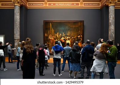 amsterdam, netherlands - 2019.06.14:  rijksmuseum, people admiring the night watch painting by rembrandt van rijn