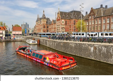 Amsterdam, Netherlands - 22 April 2019: Tourists sightseeng at Canal Boat City Hopper near the Central Station of Amsterdam.