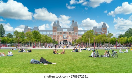Amsterdam, The Netherlands - 23th July 2020 - Tourists sitting on the grass of the museum square in front of the Rijksmuseum (federal museum) in the center of Amsterdam