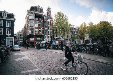 Amsterdam, Netherlands - 25 April, 2017: Adult woman rides a bicycle in historical part of Amsterdam with typical traditional houses.