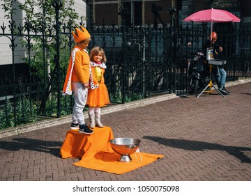 Amsterdam, Netherlands - 27 April, 2017: Street performance of Little Boy and Girl are in the King and Queen on Day of the King in Amsterdam