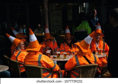 Amsterdam, Netherlands - 27 April, 2017: Group of people wearing orange costumes with hat like traffic cone on Day of the King in Amsterdam