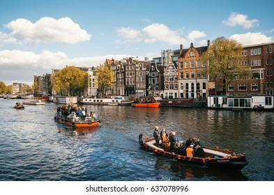 Amsterdam, Netherlands - 27 April, 2017: : Local people and tourists dressed in orange clothes ride on boats and participate in celebrating Queensday along the canal of Amsterdam.