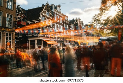 Amsterdam, Netherlands - 27 April, 2017: Streets of Amsterdam full of people in orange during the celebration of Queensday. Blurred people at sunset with sunlight and orange decorations.
