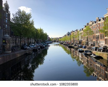 Amsterdam, the Netherlands, 3 May 2018: sunny canals in Amsterdam with houses, boats and bicycles on a spring morning.
