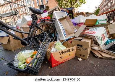 Amsterdam, Netherlands - 5 Nov. 2018:  Bikes, paper and plastic trash, and uneaten food is thrown in piles after the closing of Albert Cupytmarkt in Amsterdam. Wasteful littering in the city.