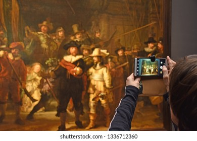 Amsterdam, The Netherlands, 7 March 2019 - Visitors are watching and taking pictures of Rembrandt's De Nachtwacht (The Night Watch) in the Rijksmuseum.