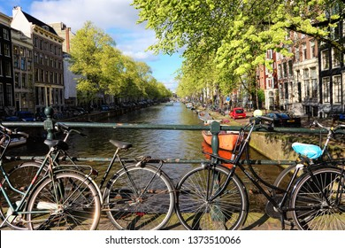 AMSTERDAM, NETHERLANDS - APR 08, 2017 : Spring on Amsterdam. Dutch traditional canal street. Sightseeing and residential boats on water. Bicycles are parked along the stone embankment and  bridges