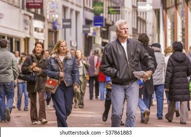 AMSTERDAM, NETHERLANDS - APRIL 10, 2006: People stroll on Kalverstraat, in downtown Amsterdam's popular shopping street.