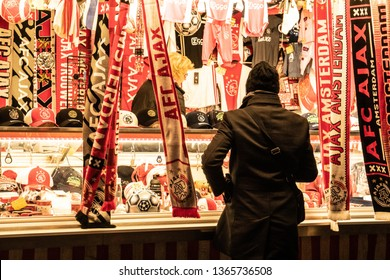 Amsterdam, The Netherlands - April 10, 2019: Supporters of soccer / football during Ajax - Juventus match. Outside at the Merchandise boot stand in Amsterdam looking at Ajax supporter scarfs.