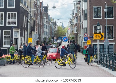 Amsterdam, The Netherlands - April 13, 2019: Street view city centre in spring with bicycles, tourists and in the background a tower of the Rijksmuseum. View from Skinny Bridge (Magere Brug).